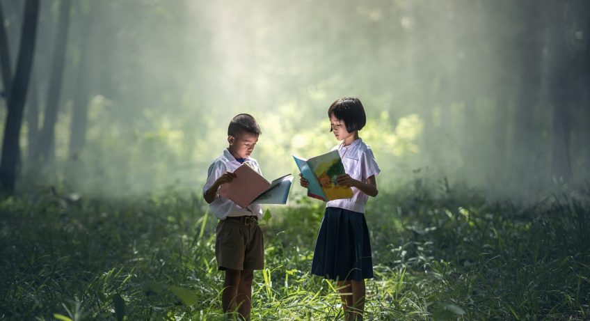 a boy and a girl reading a book