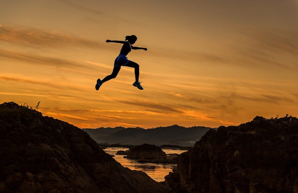 Girl achieving, jumping mountains